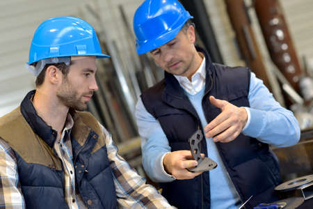 engineering: Engineer with mechanical worker checking on production