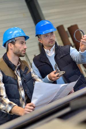 ingeniero: Ingeniero con el trabajador mec�nico de cheques en la producci�n Foto de archivo