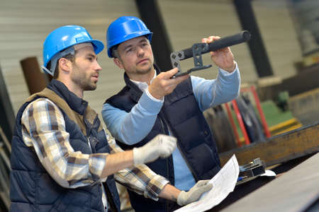 mechanical men: Engineer with mechanical worker checking on production