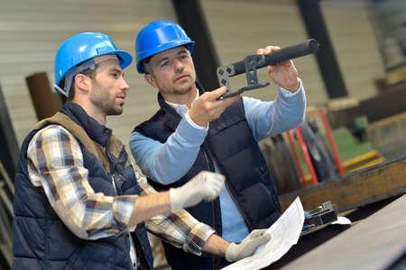 ingenieria industrial: Ingeniero con el trabajador mecánico de cheques en la producción Foto de archivo