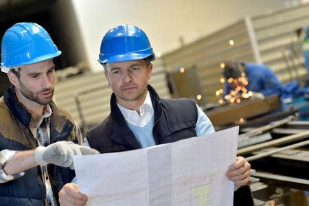 seguridad industrial: Ingeniero con el trabajador mecánico de cheques en la producción Foto de archivo