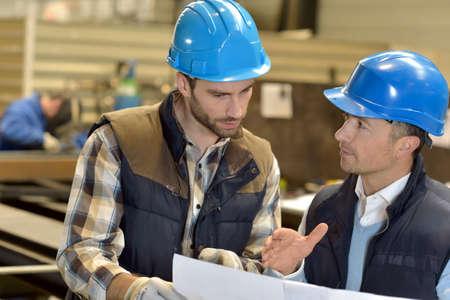 mecanica industrial: Ingeniero con el trabajador mec�nico de cheques en la producci�n Foto de archivo