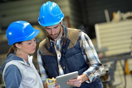 ingenieria industrial: Ingenieros en la fábrica de acero que trabajan en la tableta digital Foto de archivo