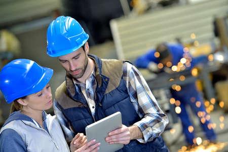 Gli ingegneri in fabbrica di acciaio che lavorano su tavoletta digitale Archivio Fotografico - 36001453