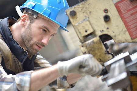 steel factory: Industrial worker working on machine in factory Stock Photo