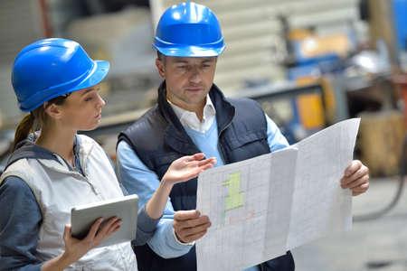 mecanica industrial: Ingenieros en instrucciones de lectura mec�nica de f�brica Foto de archivo
