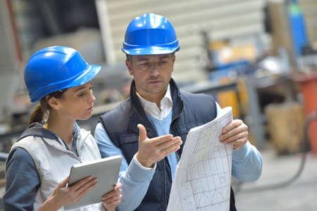 Ingenieurs in mechanische fabriek lezen instructies