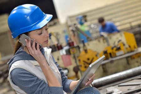 mecanica industrial: Mujer en f�brica hablando por tel�fono m�vil