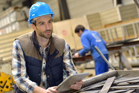 manufacturing equipment: Engineer in metallurgical factory using tablet