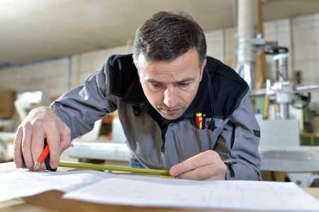 measuring tape: Closeup of carpenter using measuring tape