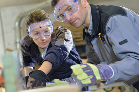 Instructor showing trainee how to use sawing machine photo