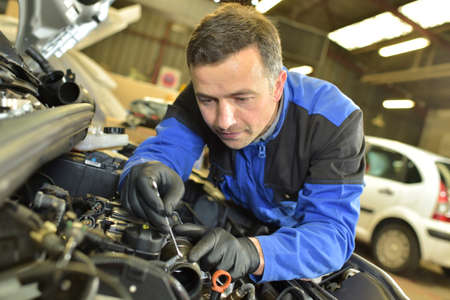 control de calidad: Técnico que trabaja en taller de reparaciones auto