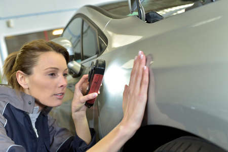 car manufacturing: Woman technician working in auto bodywork shop