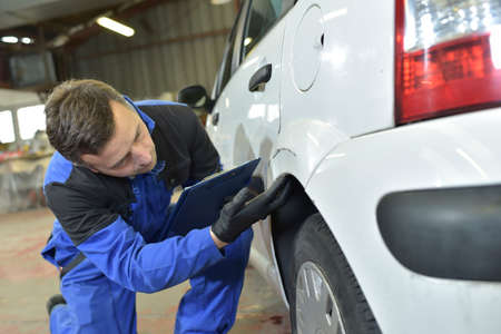 bodywork: Mechanic checking on auto bodywork Stock Photo
