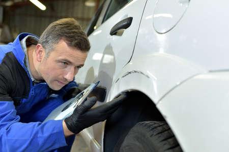 Mechanic checking on auto bodywork Archivio Fotografico
