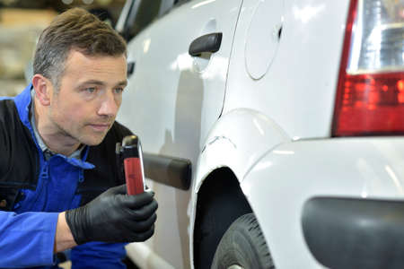 mechanician: Mechanic checking on auto bodywork Stock Photo
