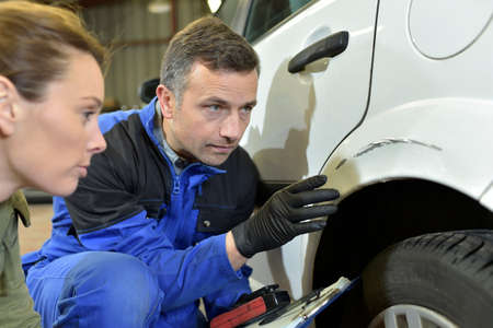 mechanician: Mechanician with insurance adjuster checking on auto repair Stock Photo