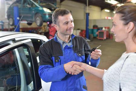 giving back: Auto repair mechanic giving car keys back to customer
