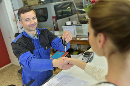 repair shop: Mechanic giving keys back to car owner