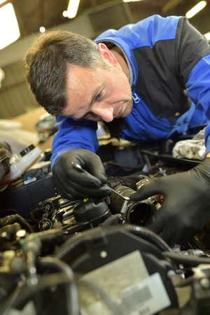 Technician working in auto repair shop photo