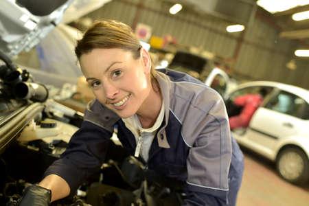 Technician woman working in auto repair workshop photo