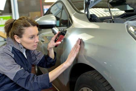 inspecting: Woman technician working in auto bodywork shop