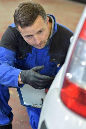 mechanician: Mechanic checking on auto bodywork Stock Photo