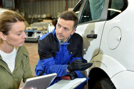 mechanician: Mechanician with insurance adjuster checking on auto repair Stock Photo