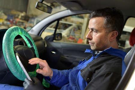 mot: Mechanic doing technical inspection on vehicle