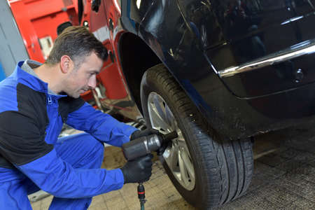 mechanician: Mechanician changing car wheel in auto repair shop Stock Photo
