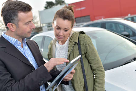 specifications: Car dealer showing car specifications to client on tablet Stock Photo