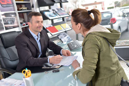 auto dealership: Car dealer editing purchase agreement to buyer Stock Photo