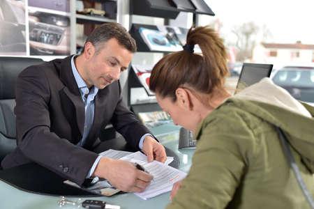 giovane donna: Giovane donna di credito di firma contrat per l'acquisto auto