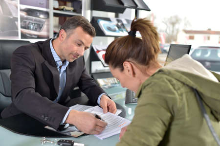 Young woman signing credit contrat for car purchase Foto de archivo