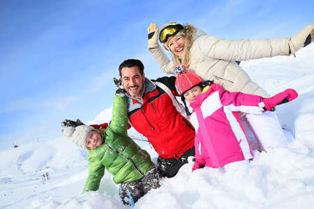 Cheerful family having good time in snowy mountain Stock Photo
