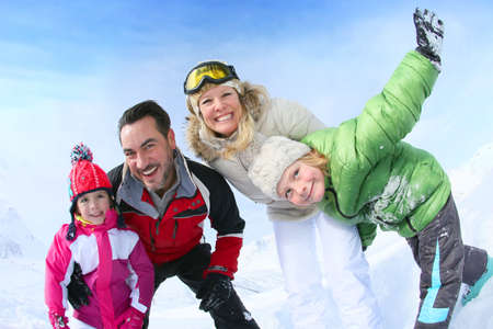 looking towards camera: Cheerful family of 4 enjoying winter vacation