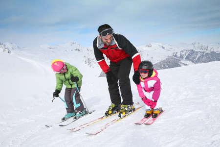 Ski-instructeur leert jonge kinderen naar beneden te gaan skipiste Stockfoto