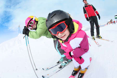 ski mask: Young girl learning how to ski with family