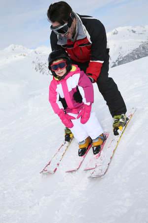 slope: Daddy with little girl skiing down slope