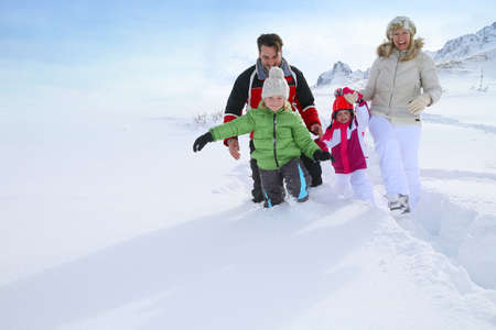 Family walking in deep snow track Archivio Fotografico