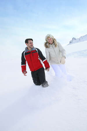 thick: Couple walking in thick snow track Stock Photo