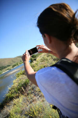 nature photo: Backpacker taking picture of Limay river, Patagonia