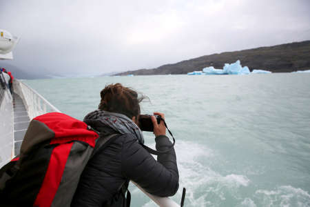 argentino: Tourist on boat taking picture of an Iceberg, Argentino Lake Stock Photo