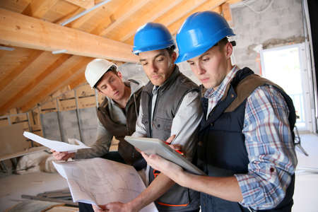 sites: Construction manager with workers checking on site Stock Photo