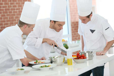 culinary chef: Chef training students in restaurant kitchen Stock Photo