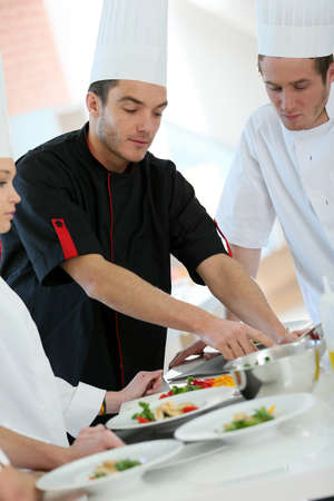 professional occupation: Chef training students in restaurant kitchen Stock Photo