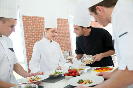 Chef training students in restaurant kitchen Stock Photo
