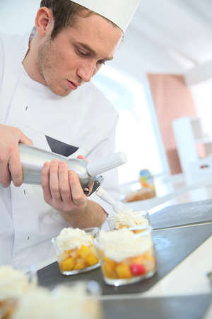 siphon: Pastry cook spreading whipped cream on dessert