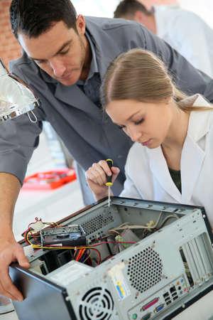 redes electricas: Profesor con los estudiantes en la tecnolog�a de la reparaci�n de la computadora Foto de archivo