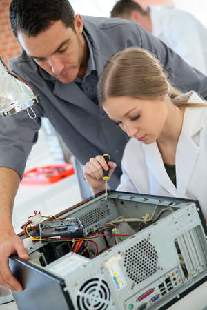 Teacher with student in technology repairing computer Stock Photo